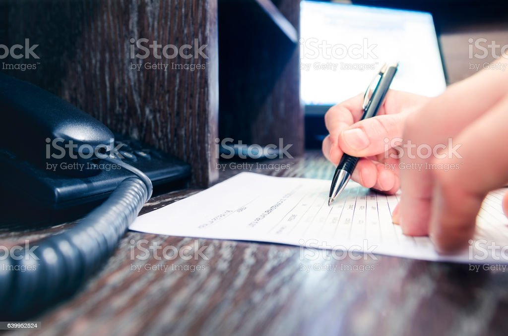 Businessman writing on paper in office stock photo