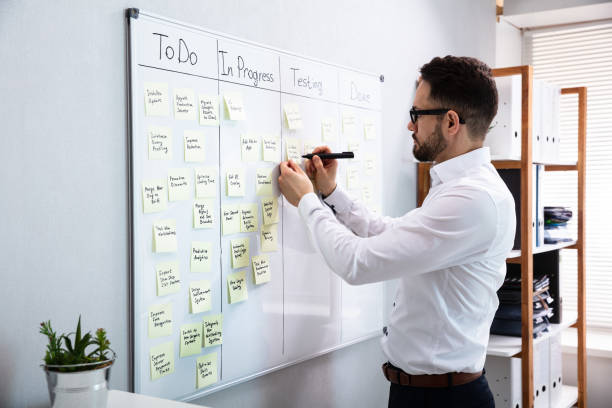 Businessman Writing On Sticky Notes Side View Of Businessman Writing On Sticky Notes Attached To White Board In Office agility stock pictures, royalty-free photos & images