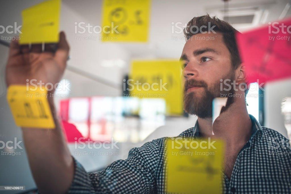 Geschäftsmann auf gelbe selbstklebende Notiz schreiben – Foto