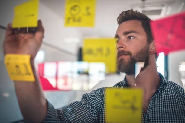 Businessman writing on yellow adhesive note stock photo