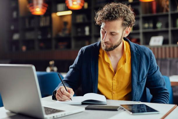 Geschäftsmann schreibt Aufgaben auf der Agenda, während er im Café sitzt. – Foto