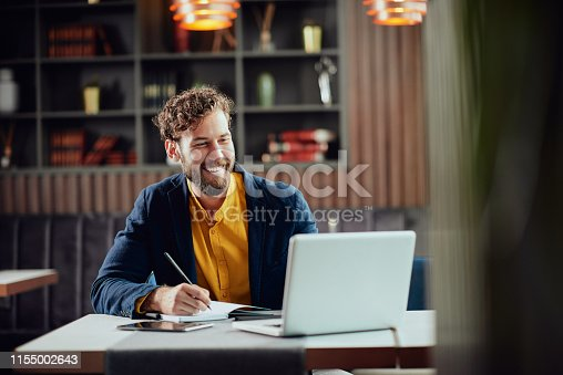 istock Businessman writing tasks in agenda while sitting in cafe. 1155002643