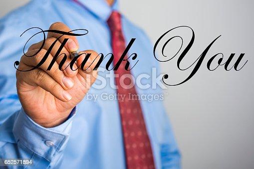 1094837778 istock photo Businessman writing Thank You word on virtual screen. 652571894