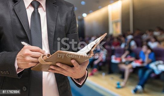 istock Businessman writing the note book on the Abstract blurred photo of conference hall or seminar room with attendee background 811762694