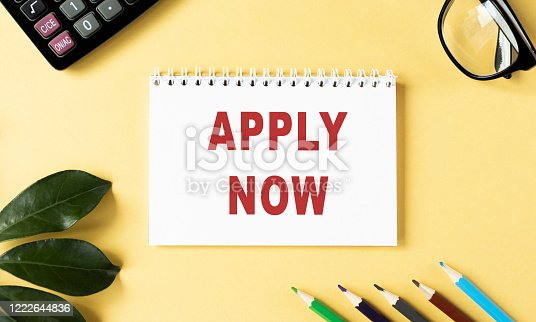 A businessman writing the words, Apply Now, on a note pad.
