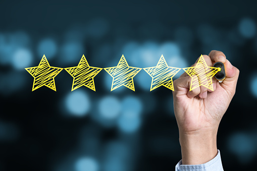 Businessman writing yellow five star to customer evaluation service and product. Marketing review and evaluation concept.