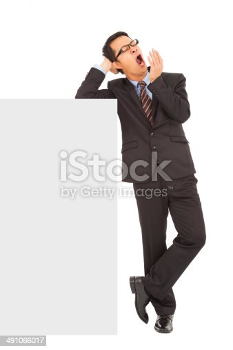 istock businessman yawning and standing  with blank board 491066017