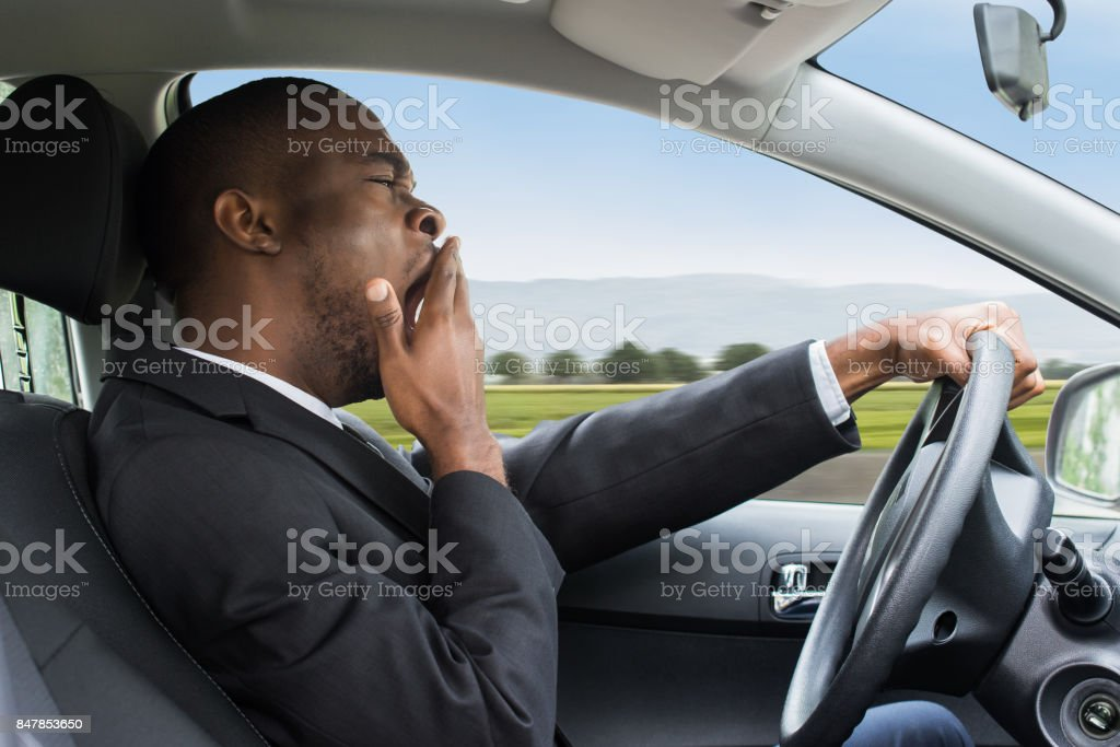 Businessman Yawning While Driving Car stock photo