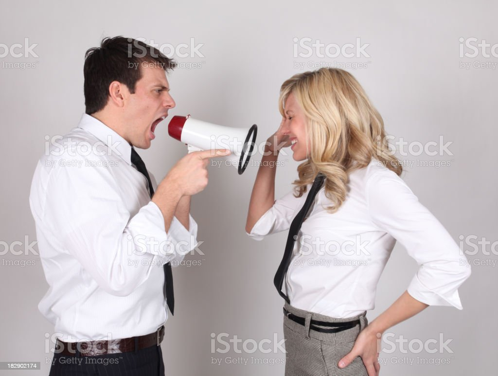 Businessman yelling at businesswoman with megaphone royalty-free stock photo