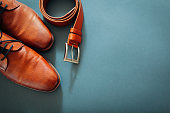 Businessman's accessories. Brown leather shoes, belt, perfume, golden rings. Male fashion. Morning of groom