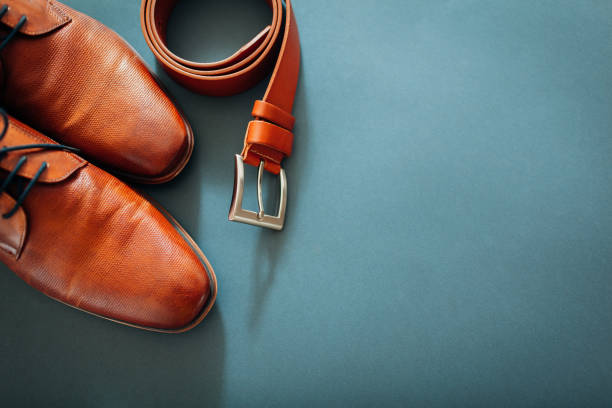 Businessman's accessories. Brown leather shoes, belt, perfume, golden rings. Male fashion. Businessman