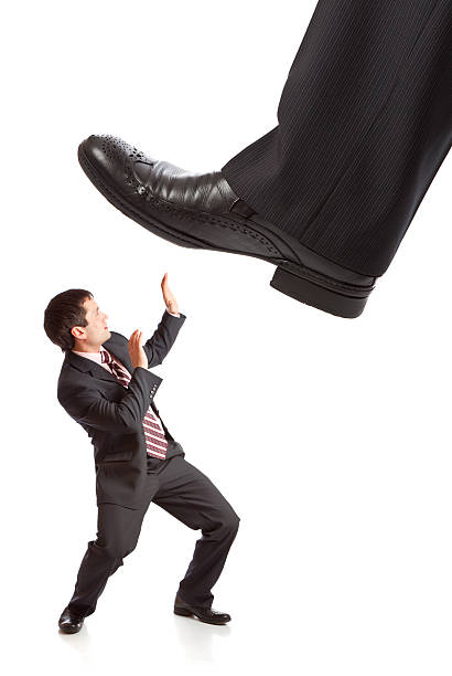 Businessman's foot stepping on tiny businessman stock photo