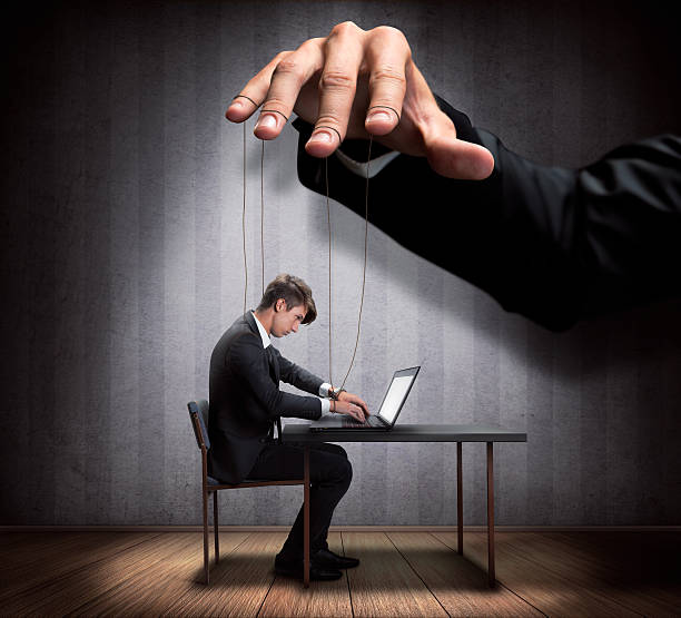 Businessman's hand controlling a worker marionette Businessman's hand controlling a worker marionette puppet stock pictures, royalty-free photos & images