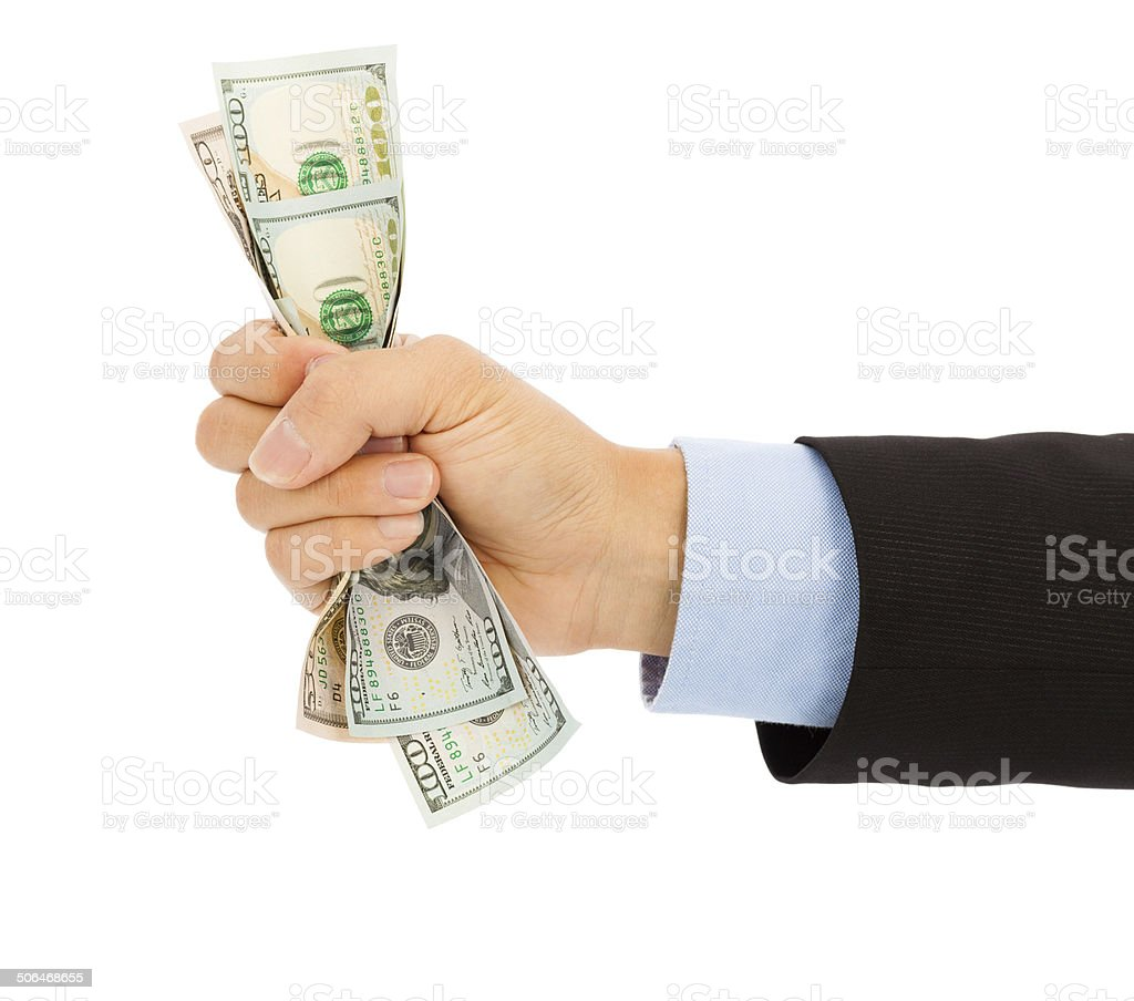 businessman's hand grasping a handful of dollars stock photo