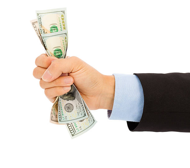 businessman's hand grasping a handful of dollars businessman's hand grasping a handful of dollars in studio handful stock pictures, royalty-free photos & images