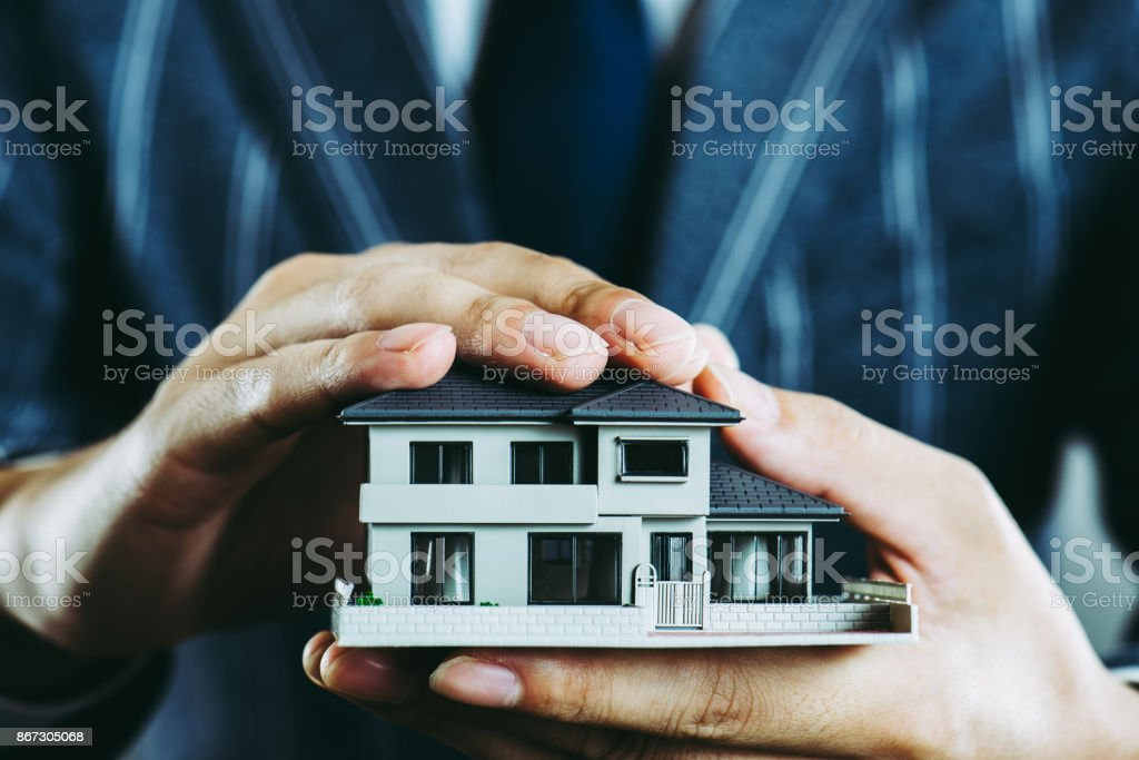 Businessman's hand holding a house model stock photo