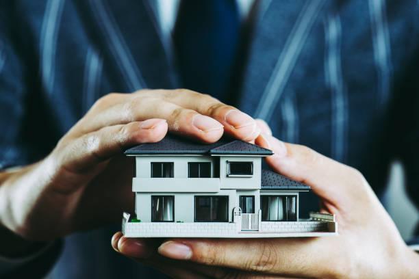 家模型を持っているビジネスマンの手 ストックフォト