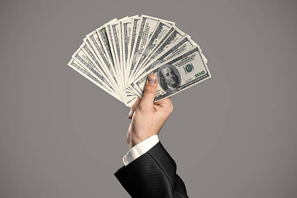 Businessman's Hand  Holding Money. Handful Of Dollars Businessman's Hand  Holding Money. Handful Of Dollars On Gray Background. handful stock pictures, royalty-free photos & images