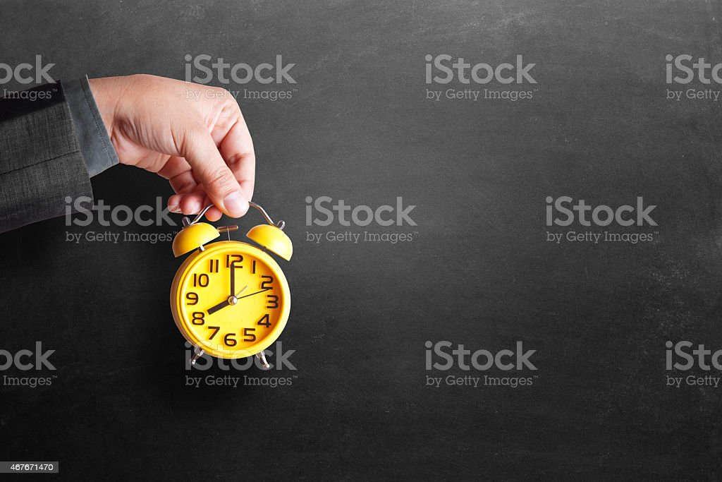 Businessman's hand holding yellow alarm clock in front of blackboard stock photo