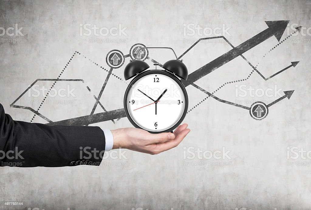 businessman's hand holds an alarm clock. A businessman's hand holds an alarm clock. There is a growing line charts behind the alarm clock. A concept of time management or billing services in legal or consulting company. 2015 Stock Photo