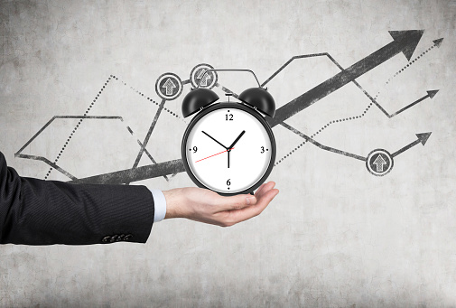 Businessmans Hand Holds An Alarm Clock Stock Photo - Download Image Now
