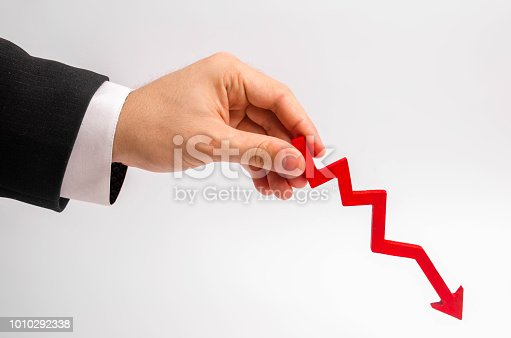 istock A businessman's hand is holding a red arrow down on a white background. The concept of reducing costs and profits, falling living standards and prices. Decreased projections, depressed economies. 1010292338