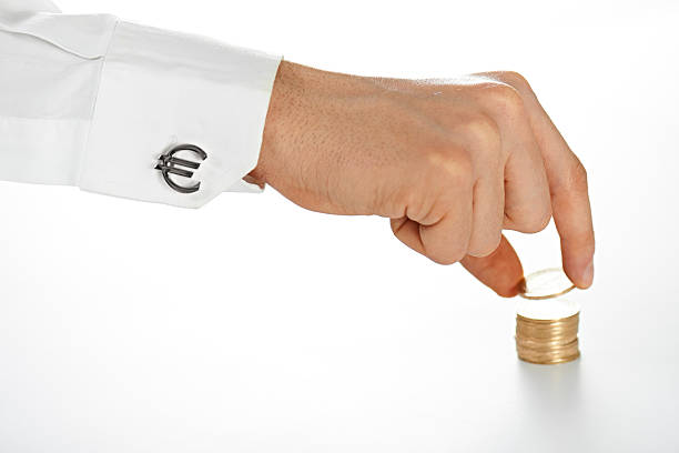 Businessman's Hand Placing Coins Close up shot of a European businessman adding coins to his savings affix stock pictures, royalty-free photos & images