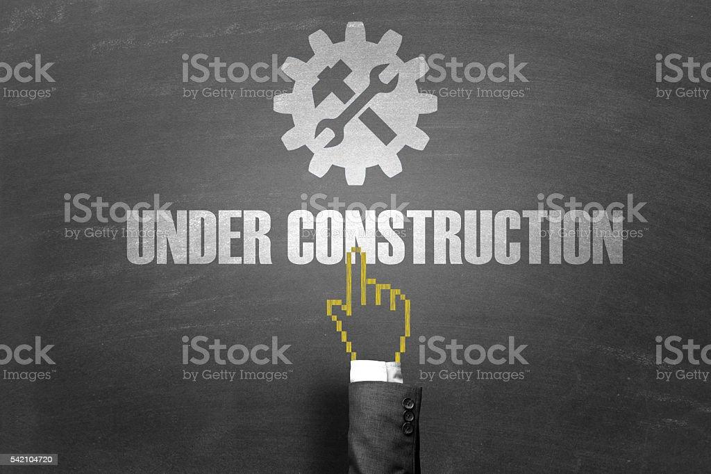 Uomo d'affari s Mano che indica per in costruzione testo - foto stock