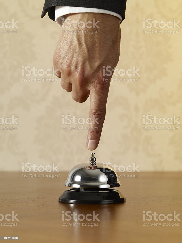 Businessman's hand ringing silver service bell stock photo