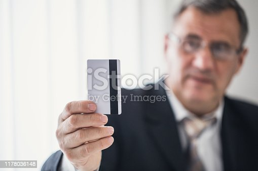 A businessman's hand shows a credit card, a cashless means of payment