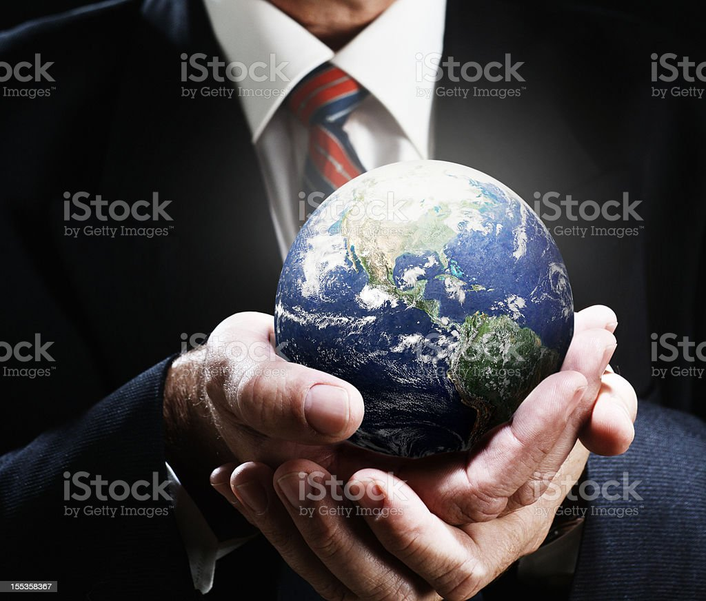 Businessman's hands carefully cradle miniature world globe royalty-free stock photo