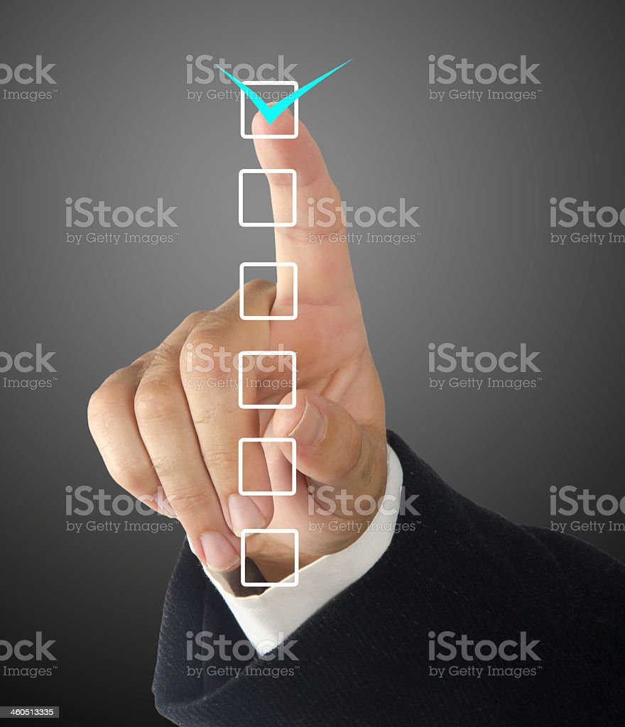 A businessman's hands checking a box on a checklist stock photo