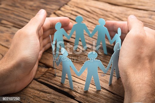 istock Businessman's Hands Covering Paper Team On Table 922107232