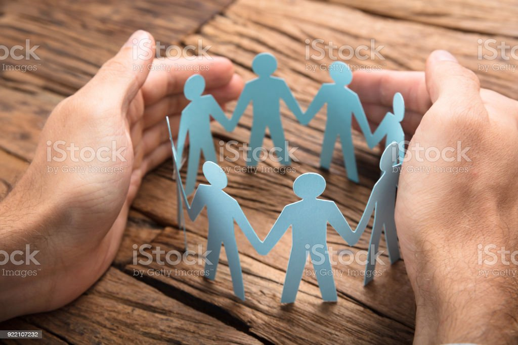 Businessman's Hands Covering Paper Team On Table stock photo