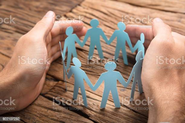 Businessmans Hands Covering Paper Team On Table - Fotografias de stock e mais imagens de Adulto
