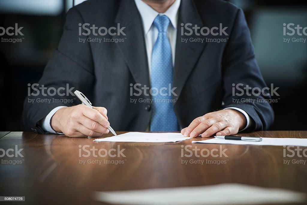 Businessman's Hands Signing on Document at his Desk royalty-free stock photo