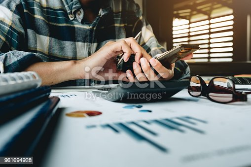 927401824 istock photo Businessman's hands smartphone and calculator on desk at the office for Financial data analyzing counting - Business Financial Concept 961694928