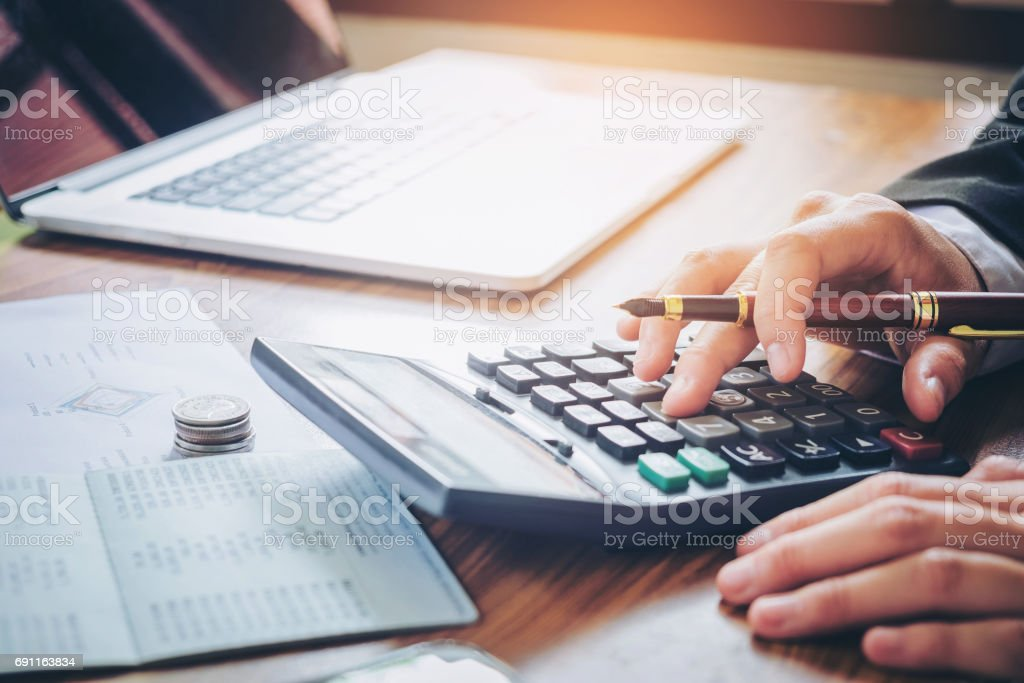 Businessman's hands with calculator and cost at the office and Financial data analyzing counting on wood desk foto stock royalty-free