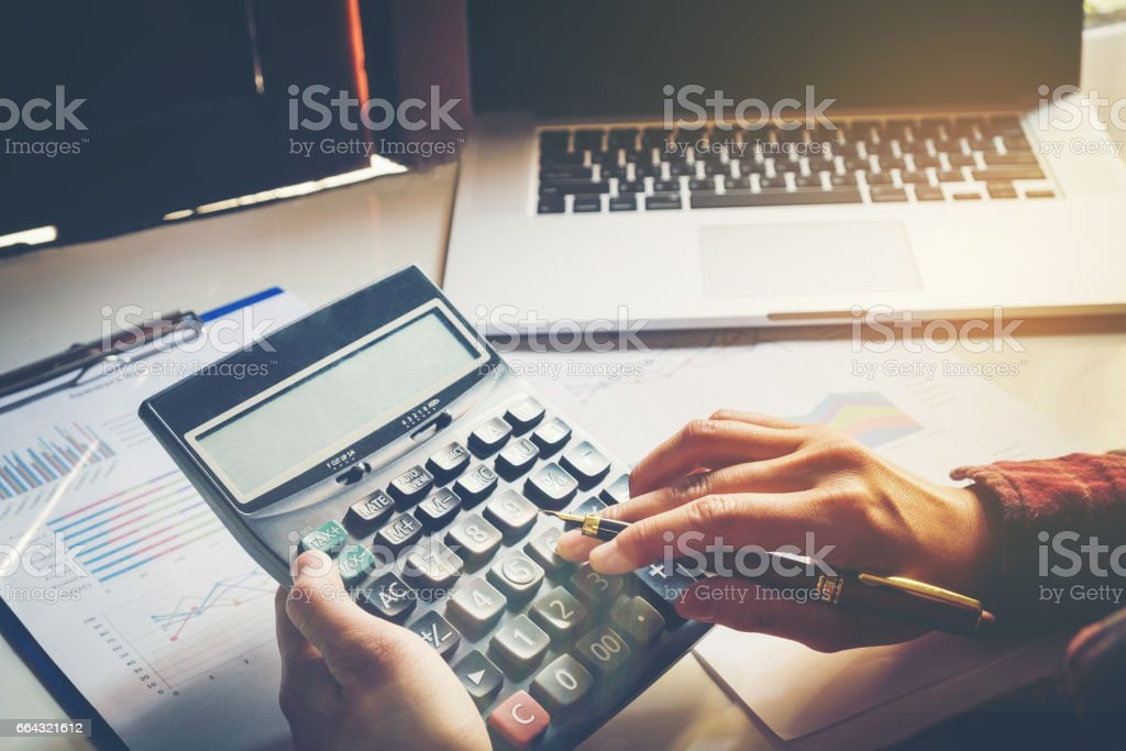 Businessman's hands with calculator and using laptop at the office and Financial data analyzing counting on wood desk stock photo