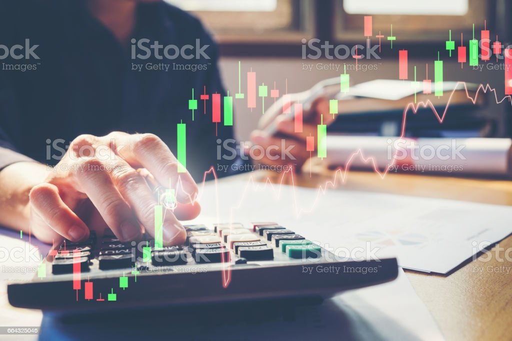 Businessman's hands with calculator at the office and Financial data analyzing counting on wood desk - foto stock