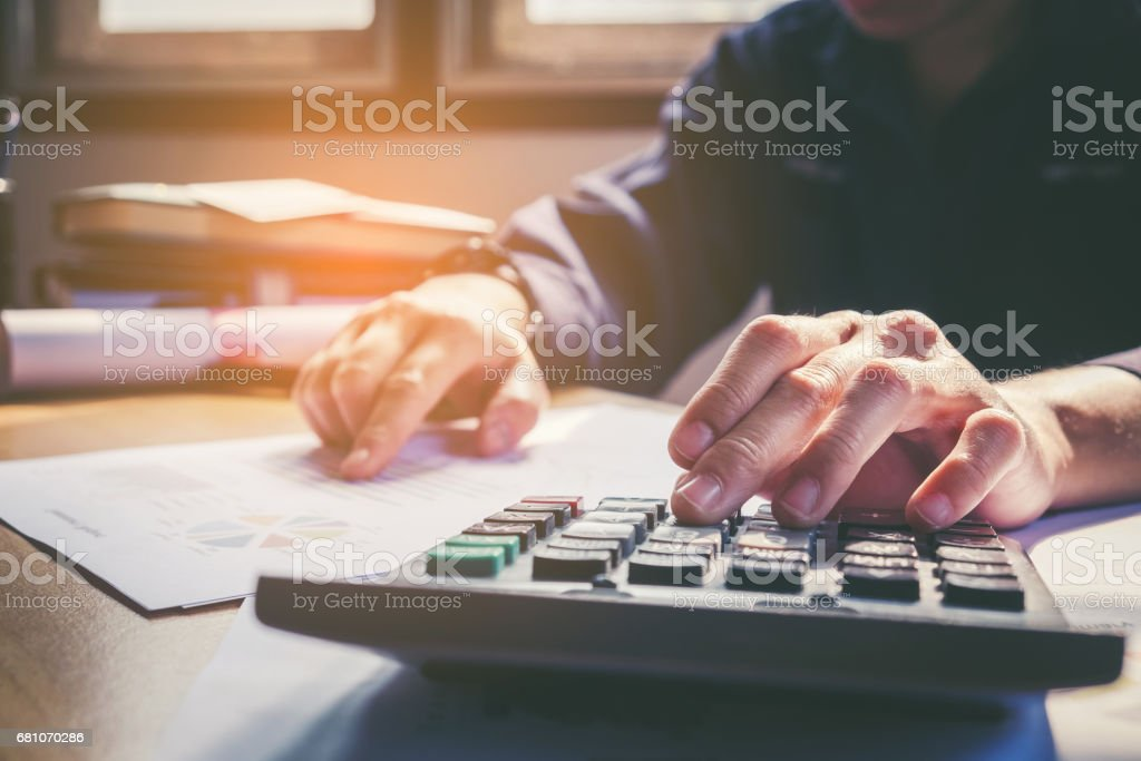 Businessman's hands with calculator at the office and Financial data analyzing counting on wood desk stock photo