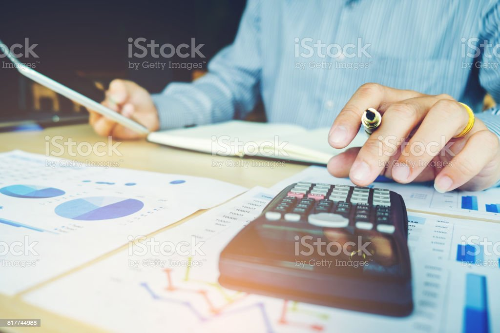 Businessman's hands with calculator at the office and Financial data analyzing counting stock photo