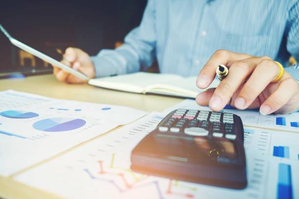 manos del empresario con la calculadora en la oficina y los datos financieros análisis de cuenta - gerente de cuentas fotografías e imágenes de stock