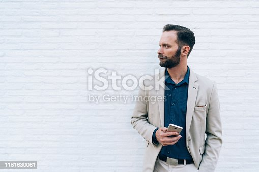 Business concept with businessman standing against white wall holding smartphone