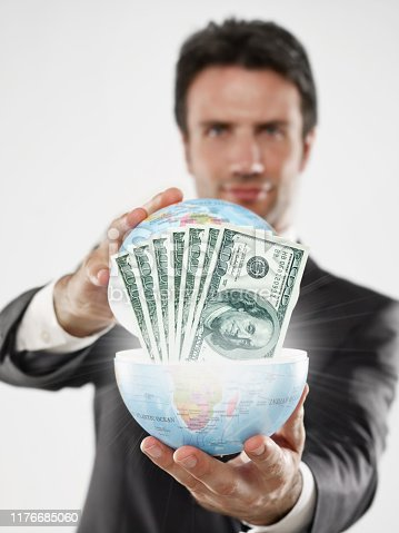 Businessman's holding a globe full of  100 dollar bills