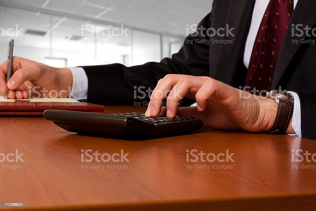 Businessmanworking working with a calculator stock photo