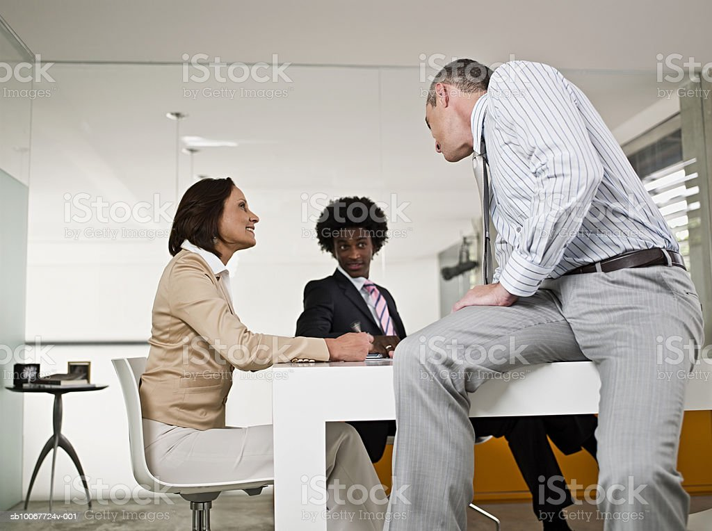 Businessmen and businesswoman talking in office royalty-free stock photo