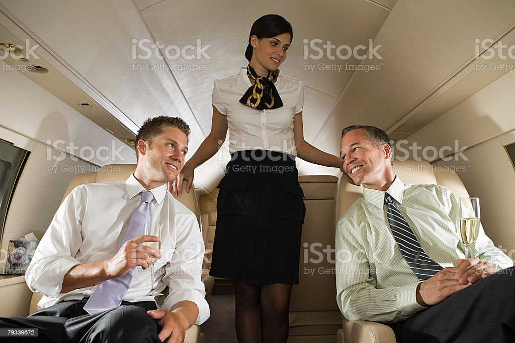 Businessmen and stewardess on jet Lizenzfreies stock-foto