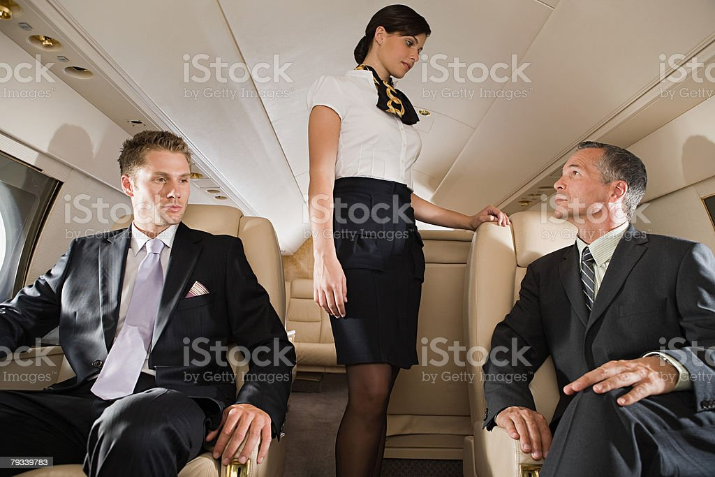 Businessmen and stewardess on jet royalty-free stock photo
