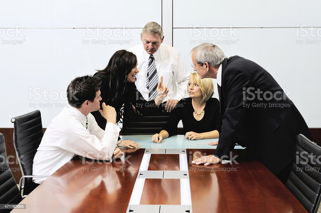 Businessmen and women arguing at a meeting stock photo